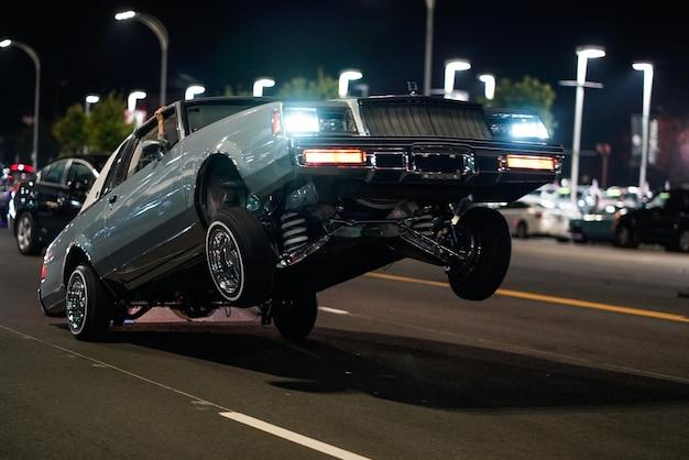Foto aproximada de um carro retrô com apenas as rodas traseiras no chão em uma rua à noite