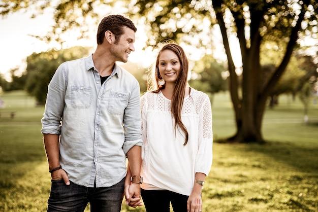 Foto aproximada de um casal de mãos dadas enquanto sorri com um fundo desfocado
