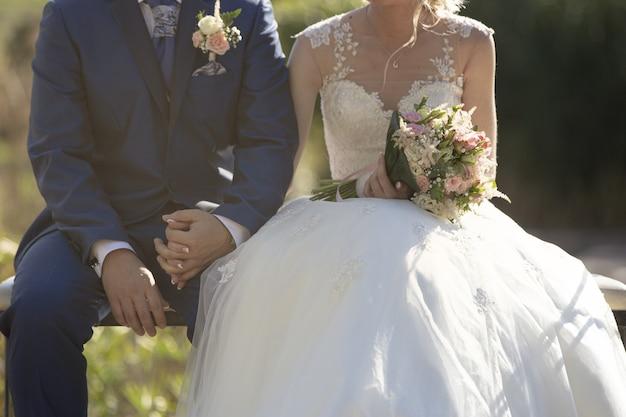 Foto aproximada de um casal recém-casado sentado em um banco, de mãos dadas