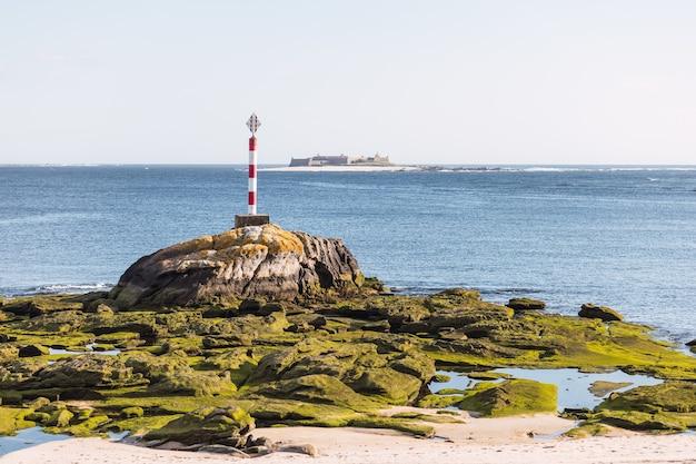Foto aproximada de um farol em uma costa rochosa