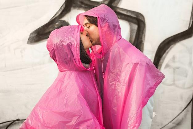 Foto aproximada de um homem e uma mulher com capas de chuva de plástico rosa se beijando