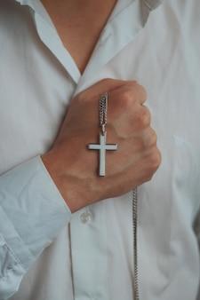 Foto aproximada de um homem religioso segurando um colar de prata com uma cruz pendente