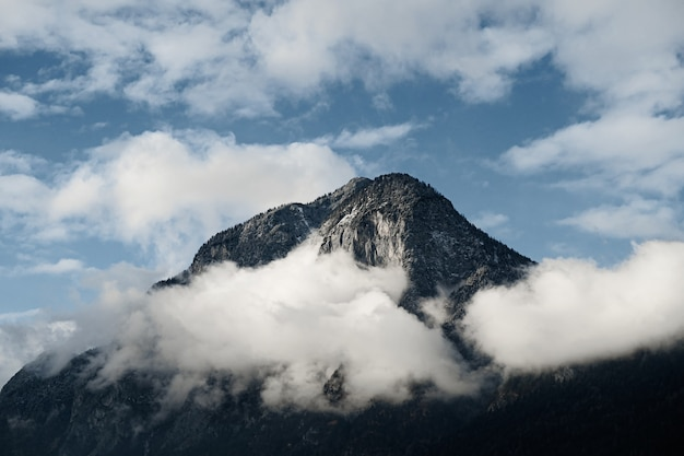 Foto aproximada de um pico de montanha parcialmente coberto por nuvens