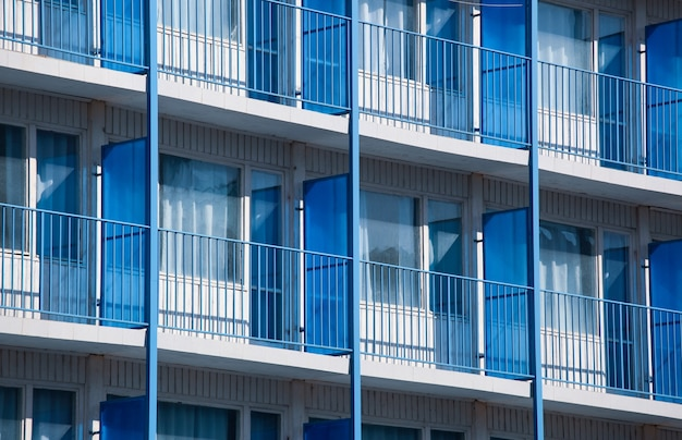 Foto aproximada de um prédio de apartamentos com divisórias de varanda azuis