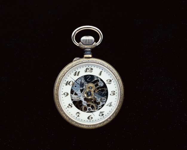 Foto aproximada de um relógio de bolso vintage em uma superfície preta