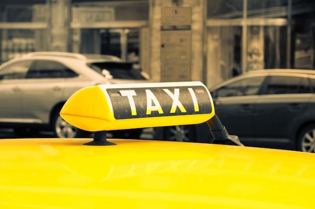 Foto aproximada de um sinal de táxi em um carro amarelo em uma rua