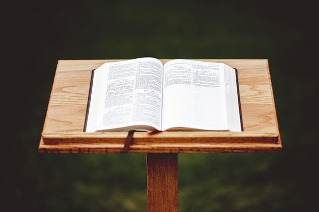 Foto aproximada de um suporte de discurso de madeira com um livro aberto
