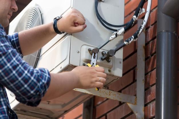 Foto aproximada de um técnico do sexo masculino consertando a unidade de ar condicionado externa