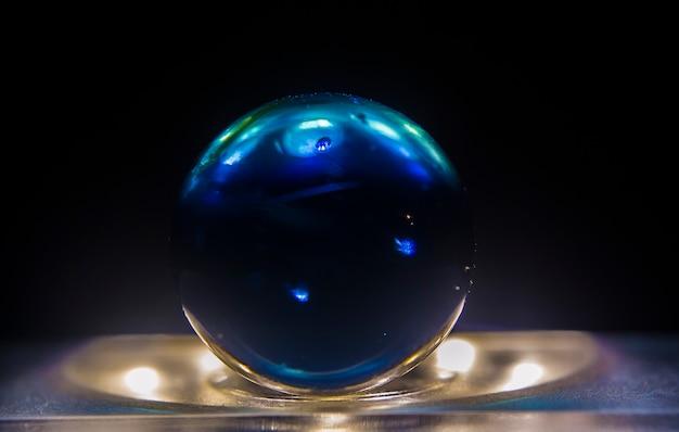Foto aproximada de uma bola de gude azul escura em cima de uma superfície iluminada com um fundo escuro