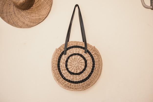 Foto aproximada de uma bolsa e um chapéu pendurados na parede