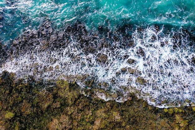 Foto aproximada de uma costa com ondas quebrando de um mapa 3d na tela