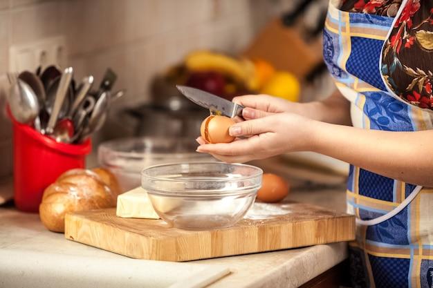 Foto aproximada de uma dona de casa quebrando um ovo com uma faca
