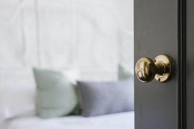 Foto aproximada de uma maçaneta de ouro em uma porta preta