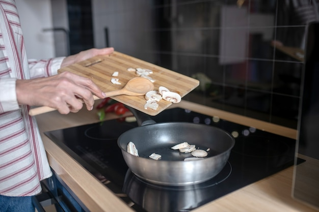 Foto aproximada de uma mulher colocando vegetais em uma frigideira