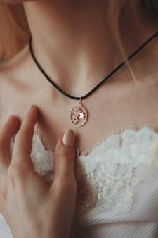 Foto aproximada de uma noiva usando um colar pendente com um cordão preto