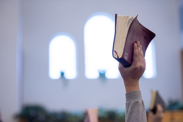 Foto aproximada de uma pessoa segurando a bíblia com um fundo desfocado