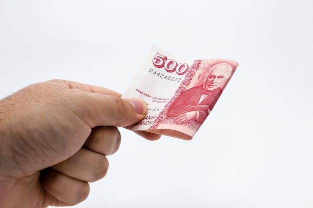 Foto aproximada de uma pessoa segurando dinheiro sobre um branco