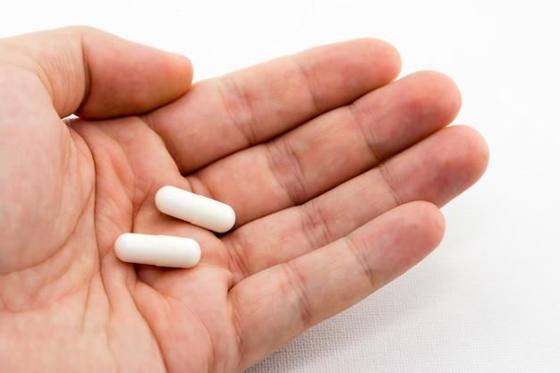 Foto aproximada de uma pessoa segurando duas cápsulas brancas