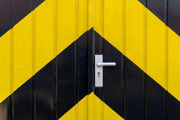 Foto aproximada de uma porta com listras pretas e amarelas