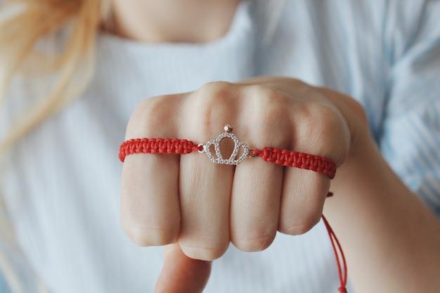 Foto aproximada de uma pulseira de fio vermelho com um pingente de coroa de prata na mão de uma mulher