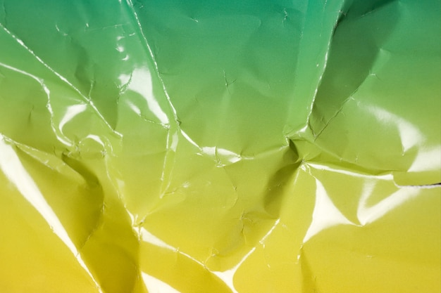 Foto aproximada de uma superfície de papelão amassada com texturas verdes e amarelas