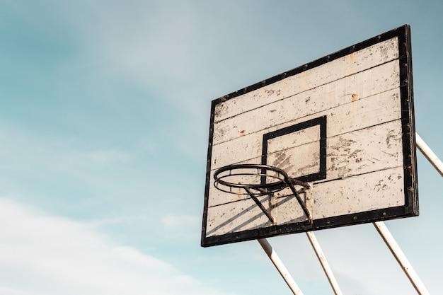 Foto aproximada de uma velha cesta de basquete sem rede em uma placa feita com aba de madeira rústica