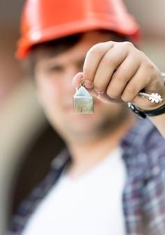 Foto aproximada do capataz segurando as chaves da nova casa na mão