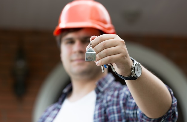 Foto aproximada do engenheiro de construção dando as chaves na casa nova