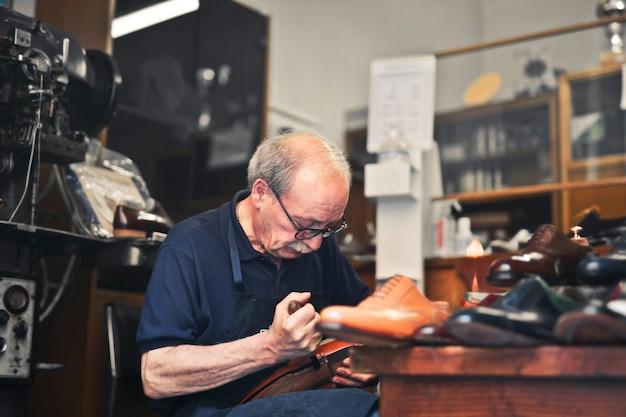 Foto aproximada do sapateiro trabalhando em sua oficina