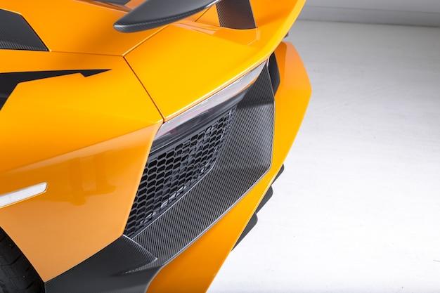 Foto aproximada dos detalhes externos de um carro esporte amarelo moderno