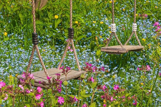 Foto aproximada dos dois balanços de madeira em um campo com flores coloridas