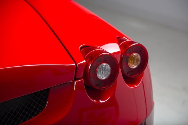Foto aproximada dos faróis de um carro vermelho moderno