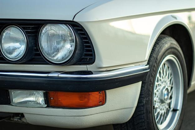 Foto aproximada dos faróis redondos de um carro clássico vintage branco