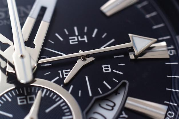 Foto aproximada dos ponteiros, números e marcas das horas de um relógio preto