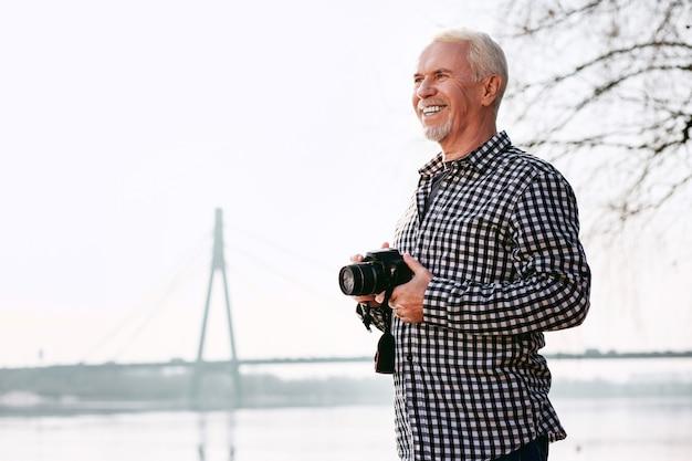 Foto arte. homem maduro positivo segurando a câmera e sorrindo