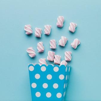 Foto artística de marshmallows na mesa azul