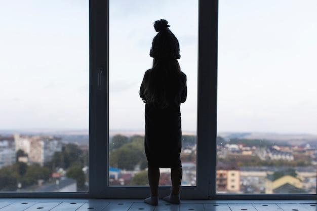 Foto artística menina ao lado da janela