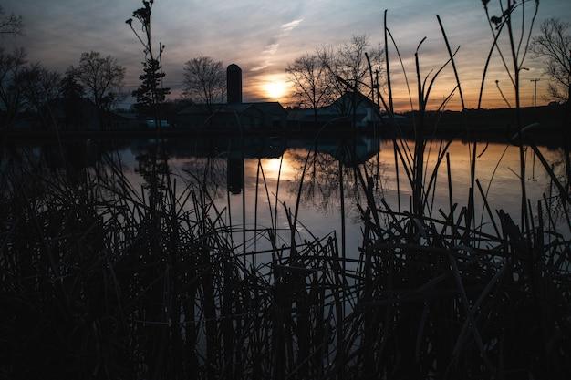 Foto assustadora de um lago com uma casa durante o pôr do sol