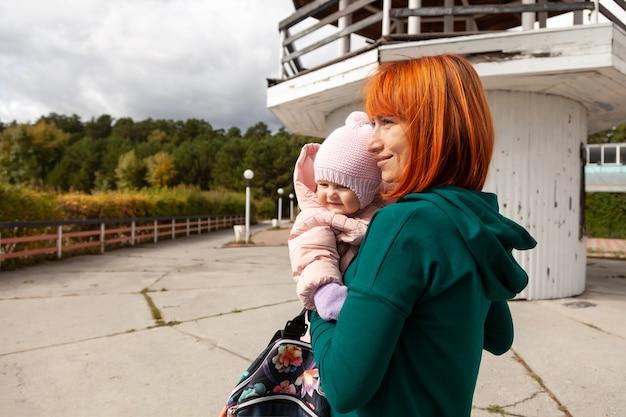 Foto atmosférica de estilo de vida de uma bela jovem ruiva em uma jaqueta verde caminha e brinca com sua filha bebê no contexto do antigo farol em um dia ensolarado de outono