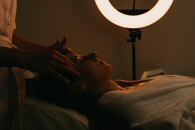 Foto atmosférica de mulher fazendo tratamento de pele facial, dermatologia, relaxamento e spa