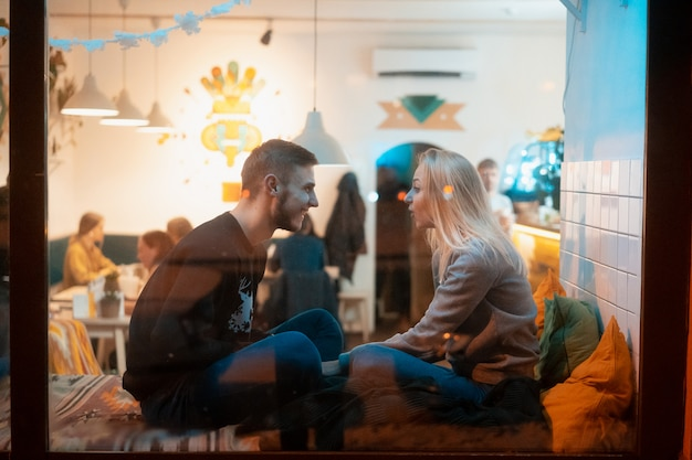 Foto através da janela. jovem casal no café com interior elegante