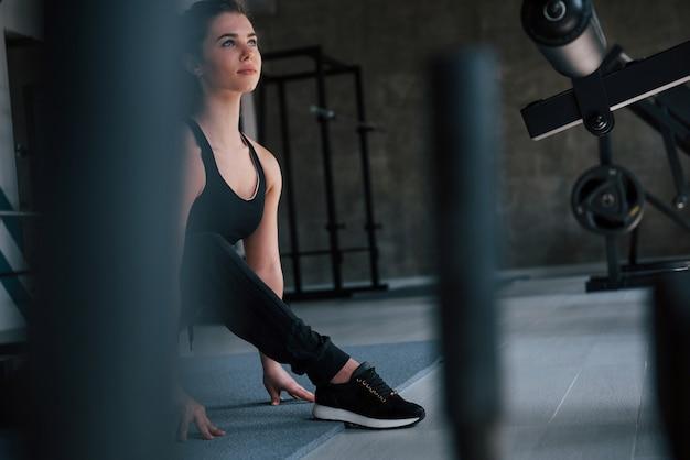 Foto através dos objetos de metal. linda mulher loira no ginásio em seu tempo de fim de semana.