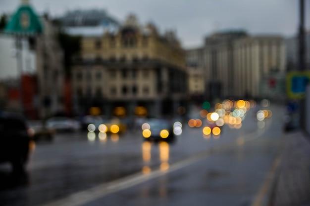 Foto borrada do fundo crepuscular da arquitetura da cidade, imagem do bokeh da rua do borrão com luzes coloridas na noite para o uso do fundo.