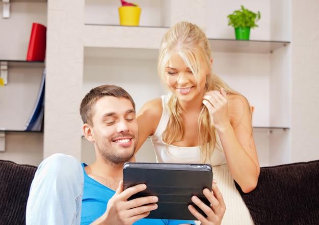 Foto brilhante de casal feliz com tablet pc (foco no homem)