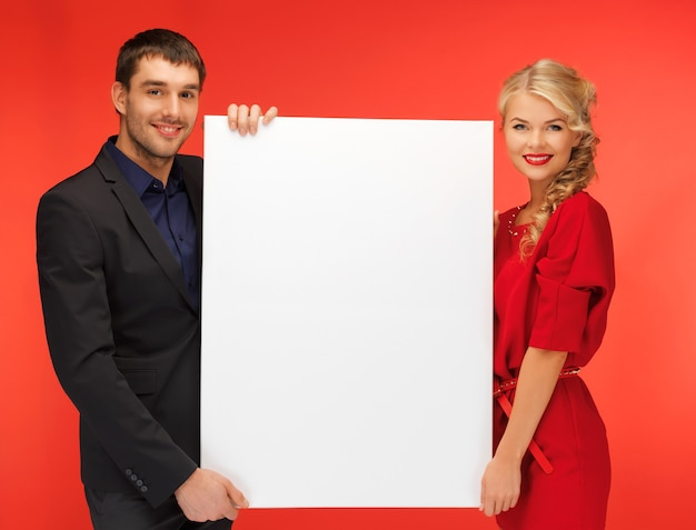Foto brilhante de casal segurando um grande quadro em branco