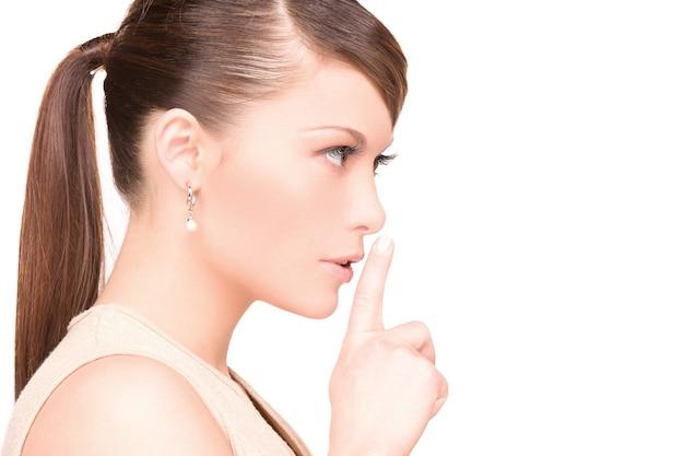 Foto brilhante de jovem com dedo nos lábios