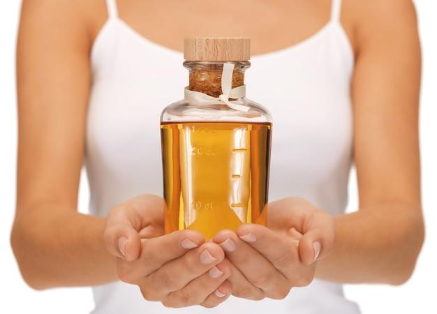 Foto brilhante de mãos femininas com garrafa de óleo