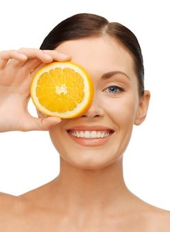 Foto brilhante de mulher bonita com uma fatia de laranja