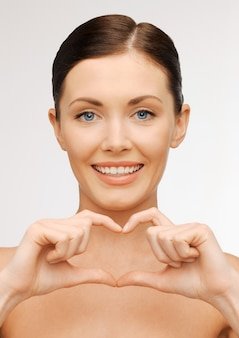 Foto brilhante de mulher bonita mostrando formato de coração