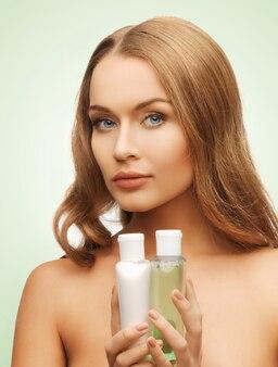 Foto brilhante de mulher com frascos de cosméticos
